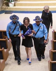 Christina Grogran is escorted out of the memorial service for her husband, Pensacola Police Department Officer Stephan Grogran, on Thursday at Olive Baptist Church in Pensacola.
