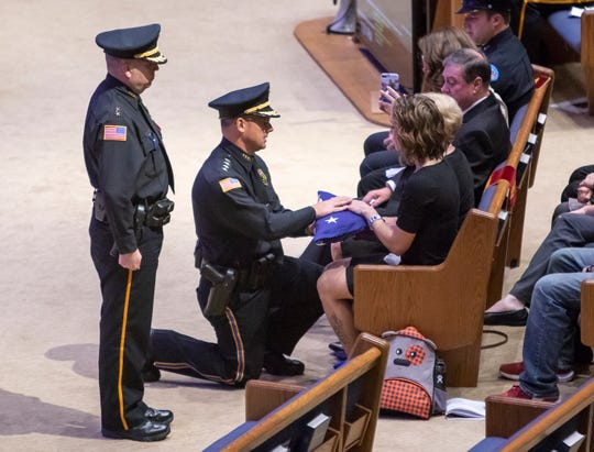 An American flag is presented to Christina Grogan during the memorial service Thursday for her husband, Pensacola Police Department Officer Stephen Grogan, at Olive Baptist Church in Pensacola.