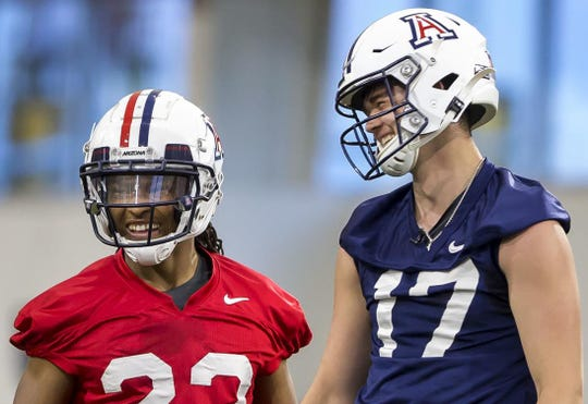 Arizona sophomore quarterback Grant Gunnell (17) laughs with senior running back Gary Brightwell (23) during Arizona first spring practice on Monday.