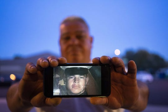 Joel Diaz Rincon, 51, holds a picture of himself when he was a U.S. Marine.