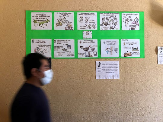 """At the El Buen Samaritano shelter in Nuevo Laredo, Mexico, tips on how to avoid the coronavirus are mounted on a bright green poster board and tacked to a front hallway wall, included: """"Don't touch your face (or anyone else's)"""" and """"Open and close doors with your shoulder or elbow. Avoid using your hands."""""""