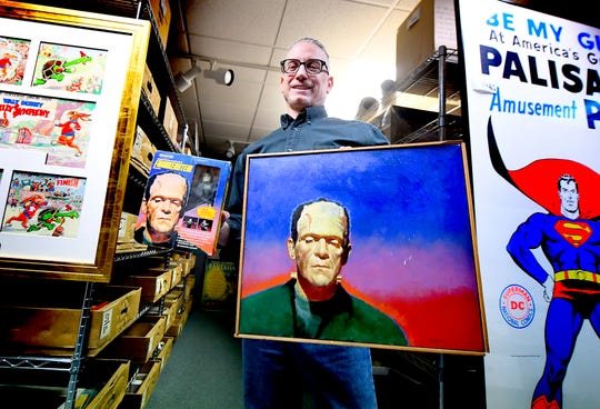 Hake's Auctions Production Manager Todd Sheffer shows original artwork in the auction room at the Springettsbury Township business, which was used on the figure's retail boxes, left, Thursday, March 5, 2020. The company is hosting an online and phone bidding auction March 11 and 12. Bill Kalina photo