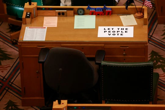 """A sign reading """"let the people vote"""" lies on the empty desk of a House Republican during a House of Representatives floor session in the Oregon State Capitol Building in Salem, Oregon, on Thursday, March 5, 2020."""