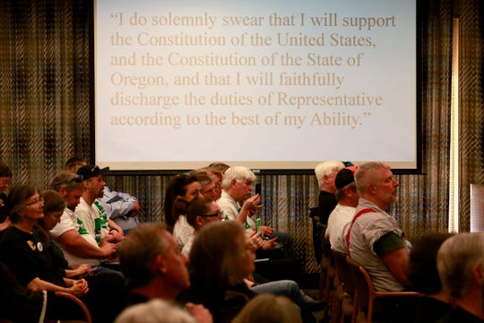 Audience members listen to a meeting of the House Rules Committee as the oath of office for Oregon representatives is projected above them in the Oregon State Capitol Building in Salem, Oregon, on Thursday, March 5, 2020.
