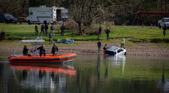 Marion County Sheriff's Office deputies look on from their boat as a tow truck pulls an SUV out of the water near the Wheatland Ferry March 5, 2020. Divers from the Clackamas County Sheriff's Office dive team located the vehicle after responding to reports of an SUV that drove off the ferry ramp and into the Willamette River on the Marion County side, just north of Keizer, the night before.