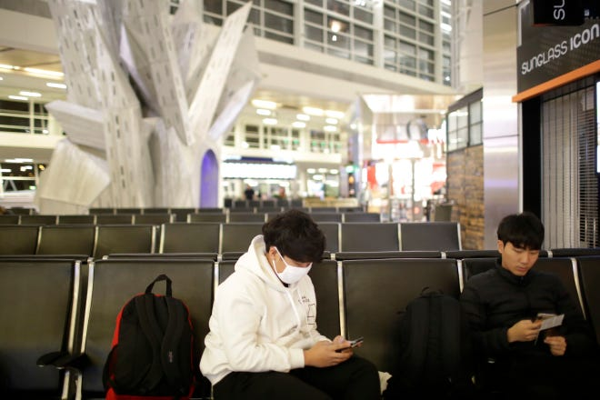 In this Thursday, Feb. 27, 2020 photo, a traveler wears a mask while waiting for a flight at Dallas Fort Worth International Airport in Texas. DFW suspended all direct flights to and from China last week according to a DFW press release. (John Roark/The Idaho Post-Register via AP)
