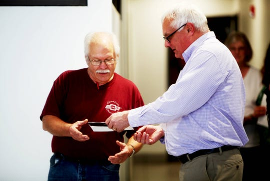 """Terry """"Joe"""" Bowler receives tickets to see the Rolling Stones from Parts Department Manager Dean Jones in celebration of working at Reliable Chevrolet for five decades."""