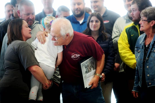 """Surrounded by family and co-workers, Terry """"Joe"""" Bowler embraces his granddaughter, Emma, during a celebration for working at Reliable Chevrolet for 50 years."""