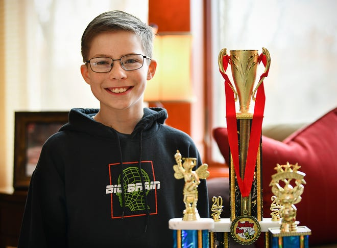 Ben St. Hilaire smiles next to his trophies earned in spelling bees Thursday, March 5, 2020, at his home in St. Cloud. St. Hilaire won the state spelling bee on Feb. 18, and will compete in the Scripps National Spelling Bee in Washington D.C.