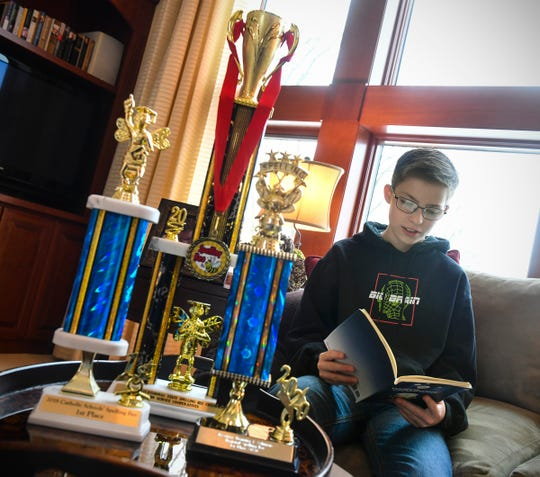 Ben St. Hilaire looks at the book of spelling words he practiced with the help of his mother Lexy to win the regional and state spelling bees Thursday, March 5, 2020, at his home in St. Cloud.