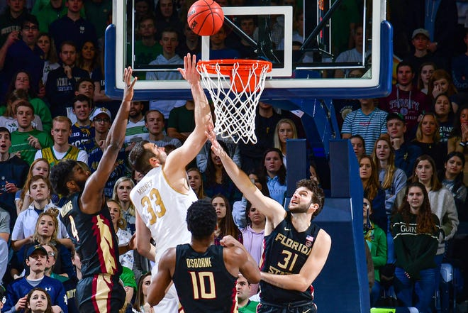 Mar 4, 2020; South Bend, Indiana, USA; Notre Dame Fighting Irish forward John Mooney (33) goes up for a shot as Florida State Seminoles forward Patrick Williams (4) forward Malik Osborne (10) and forward Wyatt Wilkes (31) defend in the first half at the Purcell Pavilion. Mandatory Credit: Matt Cashore-USA TODAY Sports