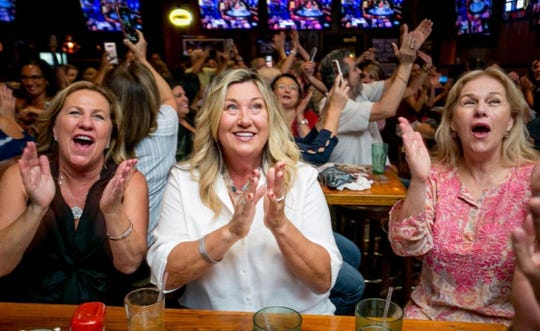 "Andrea Cameron, center, watches her son Tyler Cameron on ""The Bachelorette"" with friends Linda Barnette, left, and Susan Padilla, right, during a viewing party at Miller's Ale House in Jupiter."