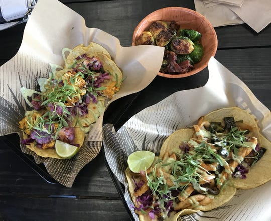 The Taco Shop has opened on the East Side, offering a creative taco menu including charred rainbow cauliflower tacos (left) and chipotle-lime roasted-chicken tacos with a cilantro-jalapeño jicama slaw (right). A tasty roasted Brussels sprouts appetizer is at the top.