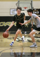 Clark Slajchert, left, goes around teammate Jack Zhao as they play a friendly game of one-on-one in the Oak Park High gym. Slajchert set several program records while climbing the county's all-time lists in a remarkable career for the Eagles.
