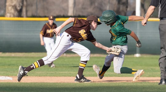 Kingsburg runner Jacob Torres gets past Golden West's Brian Gilbert  in non-league high school baseball game on Wednesday, March 4, 2020.