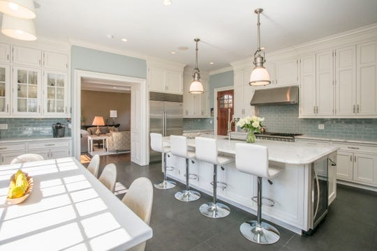 A thoughtful renovation resulted in this chef's kitchen with an immense island. It's open to a spectacular great room.