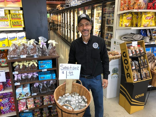 New Rochelle Farms owner Jose Filipe stands next to a basket of hand sanitizer, which has been a popular item in his supermarket located on North Avenue.