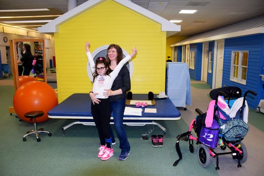 Blythedale Children's Hospital physical therapist Teresa Ann Smith incorporates 10-year-old Keira Cunningham's love of cheerleading in a recent therapy session.