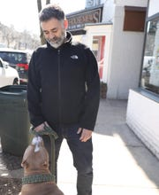Dimitrious Vagious takes a break from walking his dog Hercules to talk about how the coronavirus has slowed down business at his repair shop in Hastings March 5, 2020. Hastings school are closed Thursday and Friday because of the coronavirus.