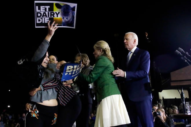 A protester at left, is held back by Biden adviser Symone Sanders, wearing stripes, face unseen, and Jill Biden, second from right, as Democratic presidential candidate former Vice President Joe Biden stands, at right, during a primary election night rally, Tuesday, March 3, 2020, in Los Angeles.