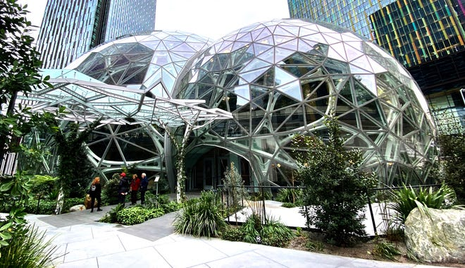 Tourists read a sign warning about the closure the Seattle Spheres at the Amazon headquarters on Thursday during an outbreak of coronavirus that prompted local authorities to recommend that people temporarily work from home and avoid large gatherings. Amazon workers largely stayed away from the campus on Thursday, the first day of the work-from-home recommendation, and access to other company facilities was restricted to workers and scheduled visitors.