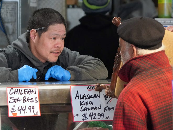 Pike Place Fish Market owner Sam Samson chats with a friend at his popular fishmonger shop in Seattle on Thursday during an outbreak of coronavirus that prompted local authorities to recommend that people temporarily work from home and avoid large gatherings.