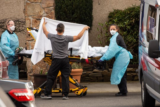 A patient is transported on Feb. 29, 2020, from the nursing facility Life Care Center, linked to at least six coronavirus deaths, onto an ambulance in Kirkland, Washington.