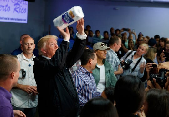 In this Tuesday, Oct. 3, 2017 photo, President Donald Trump tosses paper towels into a crowd at Calvary Chapel in Guaynabo, Puerto Rico.