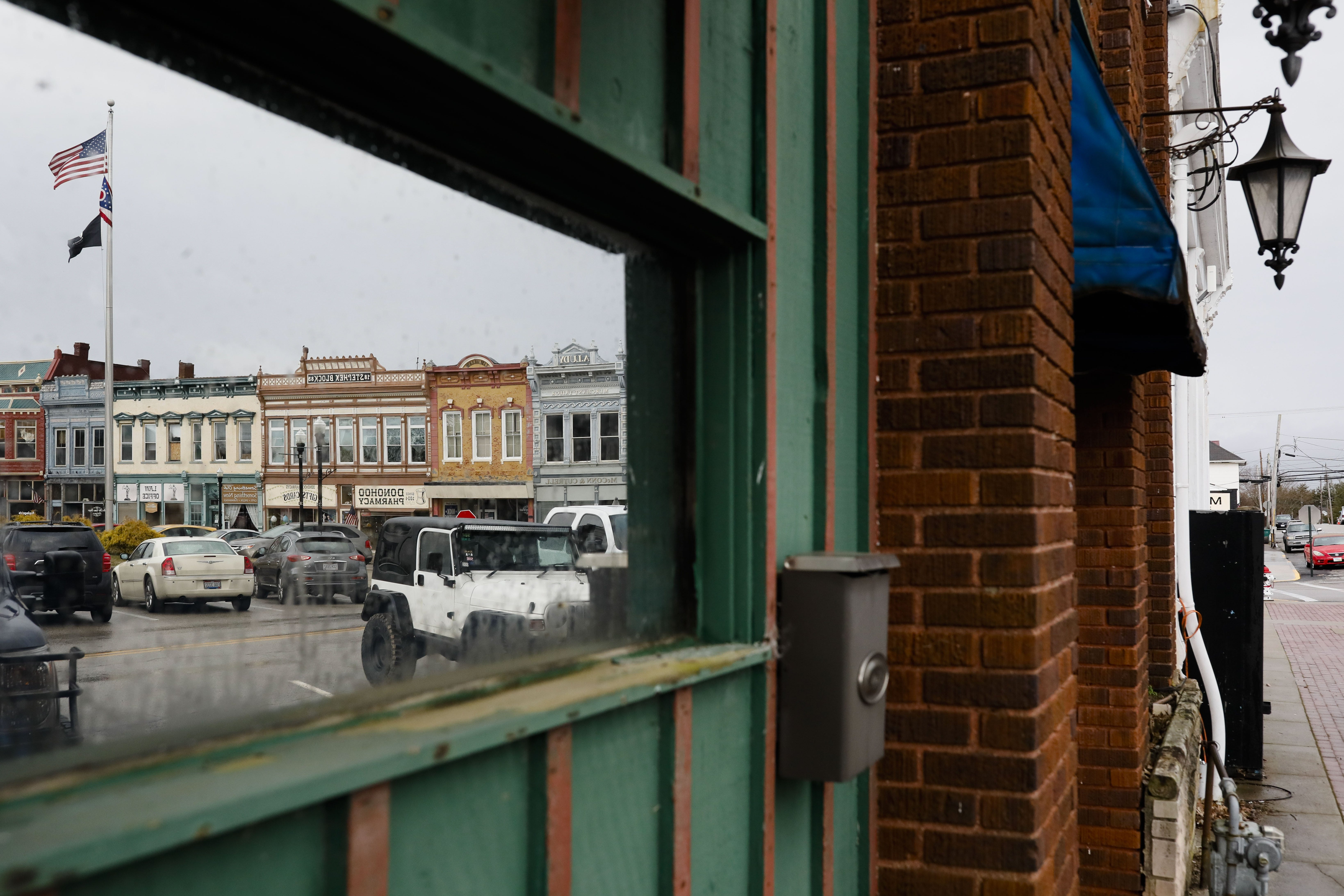 Buildings on the town square are reflected in a windown on Tuesday, March 3, 2020 in Georgetown, Ohio. [Joshua A. Bickel/Dispatch]