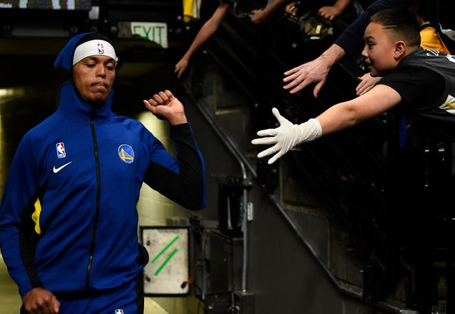 An NBA fan wearing a glove tries to high-five Damion Lee of the Golden State Warriors before a game this week. The NBA has told players to avoid contact with fans and strangers as a result of coronavirus concerns.