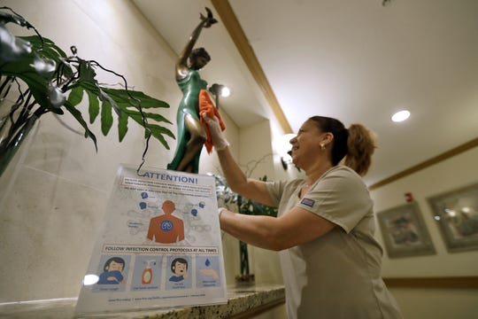 Environmental Services member Maggie Masstrapa cleans behind an infection control warning poster at the Palm Garden of Tampa Health and Rehabilitation Center, March 5, 2020, in Tampa, Fla. Health inspectors were fanning out across the country, ordered by the White House, to ensure that Medicare providers, including hospitals and nursing homes were following federal infection control policies, focusing on areas where cases of the deadly coronavirus were confirmed.