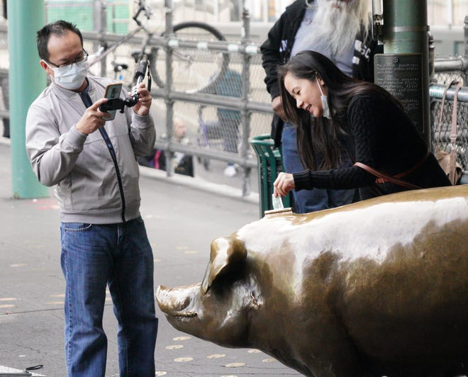 Tourists in face masks take pictures of a pig statue at the Pike Place Market in Seattle on Thursday during an outbreak of coronavirus that prompted local authorities to recommend that people temporarily work from home and avoid large gatherings.