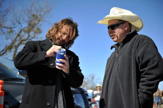 Jerrod Medulla signs a beer coozie at the inaugural Outlaws & Legends at Joe Allen's Lytle Bend Ranch in 2011.