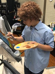 Colton Harris, an eighth-grade student at Madison Middle School, uses a cotton swab to dab white on his canvas, the finishing touch to his Bob Ross-inspired painting created during a special event Thursday. Harris, wearing a blue button-down shirt and a wig of curly hair to look like Ross, was led in the project by Madison art teacher Brady Sloane, who created the event a year ago.