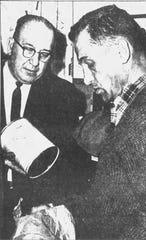 District Attorney Stephen Smyk, right, and Binghamton Det. John Gillen examine the canister involved.