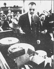 District Attorney Stephen Smyk holds a scoop used in the formula preparation during the inquest in 1962.