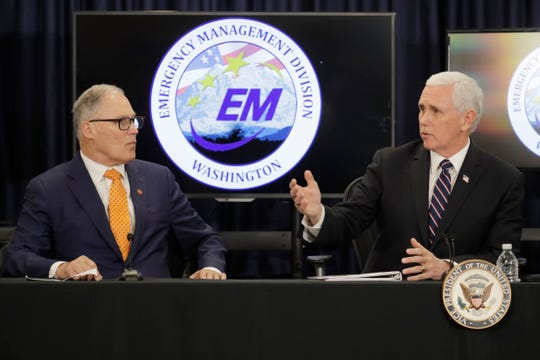 Vice President Mike Pence, right, talks with Washington Gov. Jay Inslee, left, during a meeting with officials Thursday, March 5, 2020 at Camp Murray in Washington state to discuss the state's efforts to fight the spread of the COVID-19 coronavirus.