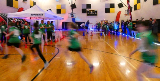 Students run into the gym as Hannah Crawford Elementary School students participate in the PTO's annual fun run on Friday.