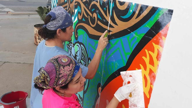 Malachy McKinney (left) and Sandra Gonzalez apply a mural to the side of the Gold Fish bar at the corner of Taylor and Mesquite streets in downtown Corpus Christi. The newly renovated bar will reopen this month.