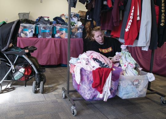 Ashley Harbur goes through some of the pajamas as her one-year old son Chad sleeps at the Children's Clothing Bank.