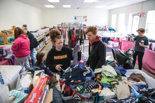 Ashley Harbur, left, from Chillicothe and her boyfriend Joe Siders from Columbus go through baby clothes at the Children's Clothing Bank located at the Chillicothe Main Library annex. Those in need can get three outfits and can get a jacket, shoes, and pajamas in addition to the outfits. The bank is open every Wednesday from 10 a.m. to noon.