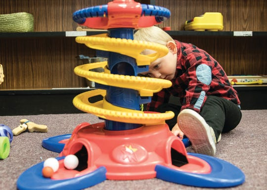 Russell looks for a small ball as he plays with a toy at the Discovery Garden indoor play area at the Chillicothe Main Library annex.