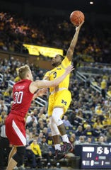 Michigan guard Zavier Simpson scores against Nebraska guard Charlie Easley during the first half Thursday, March 5, 2020 at the Crisler Center in Ann Arbor.