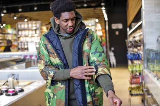 Detroit Pistons' Guard Langston Galloway, points out his personal design requests like 3/4 length sleeves  on the custom winter coat made for him by the Empowerment Plan,  a local non-profit that employs women from shelters to make winter coats that also serve as sleeping bags for the homeless,  while walking though Plum Market at the Henry Ford Detroit Pistons' Performance Center in New Center Detroit on Thursday, March 5, 2020. Each coat made for a Pistons' player is matched with a coat donation, made by the Empowerment Plan, for the homeless.