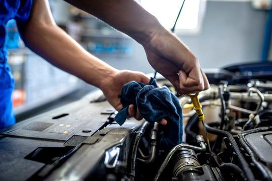 Male mechanic measuring the oil level of an engine at an auto shop.