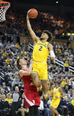 Michigan forward Isaiah Livers scores against Nebraska guard Thorir Thorbjarnarson during the first half Thursday, March 5, 2020 at the Crisler Center in Ann Arbor.