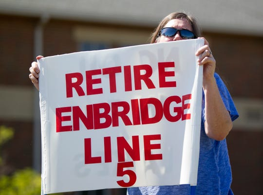 In this Thursday, July 6, 2017, file photo, Lauren Sargent, of Ann Arbor, takes part in a protest before the Enbridge Line 5 pipeline public information session at Holt High School in Holt, Mich.