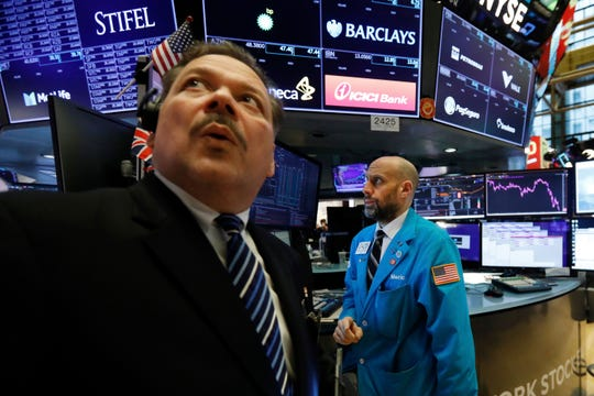 Trader John Santiago, left, looks at the numbers as he works on the floor of the New York Stock Exchange, Friday, March 6, 2020. Stocks are opening sharply lower on Wall Street and bond yields are sinking to more record lows as investors fear that economic damage from the spreading coronavirus outbreak will be longer than previously thought.