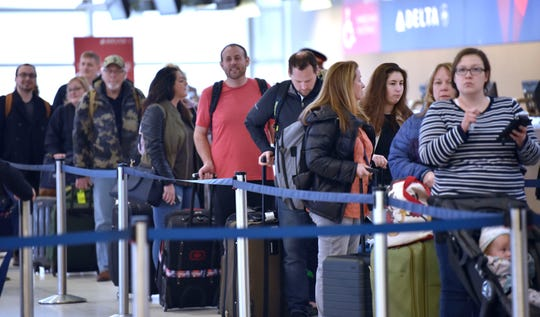 Travelers stand in line waiting to check in at the Delta counter. Travelers check into TSA security check in lines at Detroit Metro Airport, Friday morning, March 6, 2020.