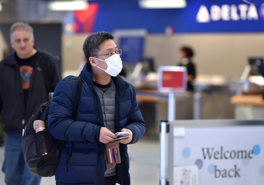 One traveler wears a mask and one does not as they approach the TSA Security check in entrance. Travelers check into TSA security check in lines at Detroit Metro Airport, Friday morning, March 6, 2020.